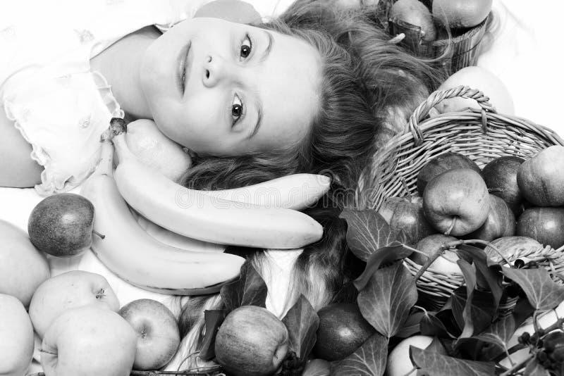 Bébé mignon s'étendant avec les fruits colorés dans le panier photo libre de droits