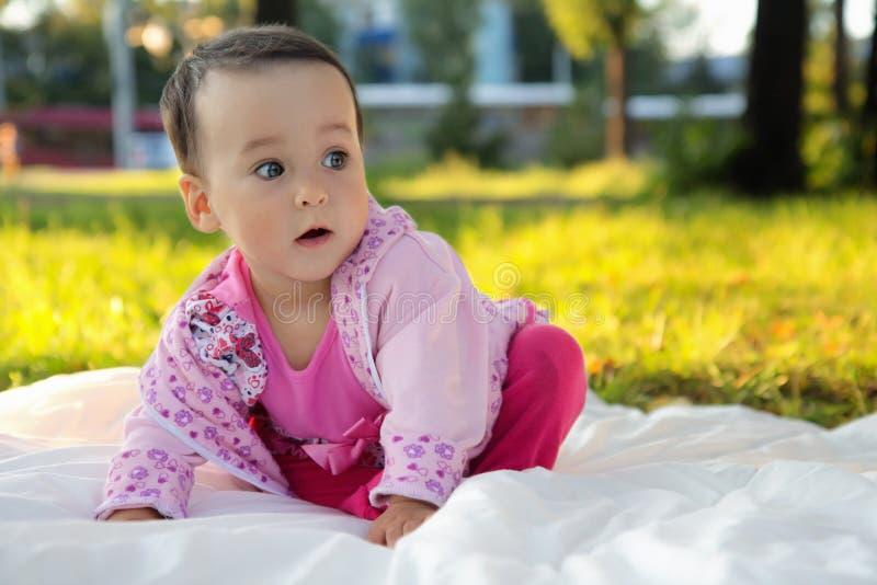 Bébé mignon s'asseyant sur l'herbe en parc photographie stock libre de droits