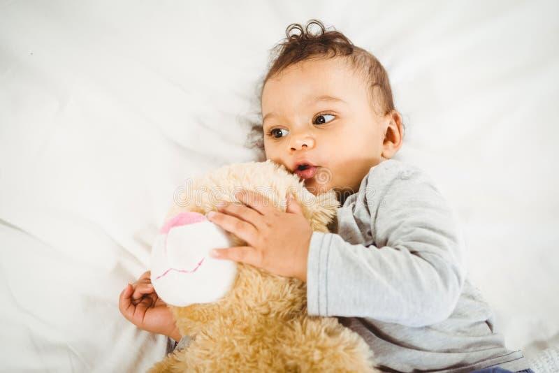 Bébé mignon tenant la peluche photos stock