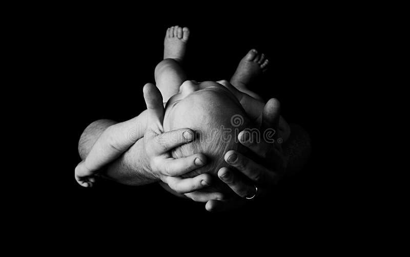 Bébé nouveau-né dans des mains de pères images libres de droits