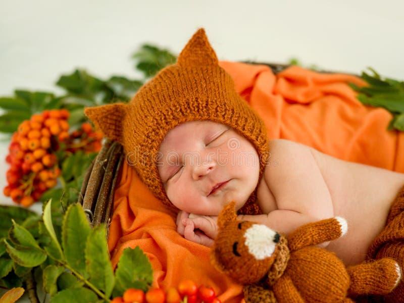 Bébé nouveau-né dans un costume tricoté par orange photos libres de droits