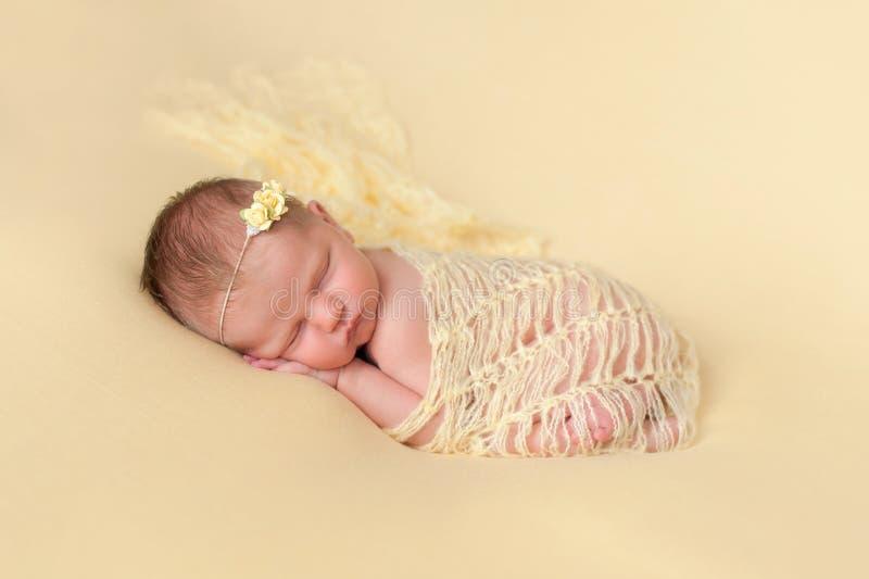 Bébé nouveau-né de sommeil enveloppé en jaune photographie stock libre de droits