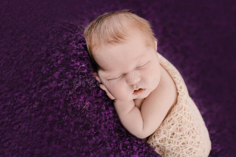 Bébé nouveau-né de sommeil sur le fond violet photo libre de droits