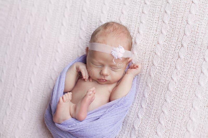 Bébé nouveau-né dormant sur un plaid rose photographie stock