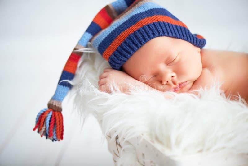 Bébé nouveau-né mignon dans le chapeau bleu de knit dormant dans le panier photographie stock libre de droits