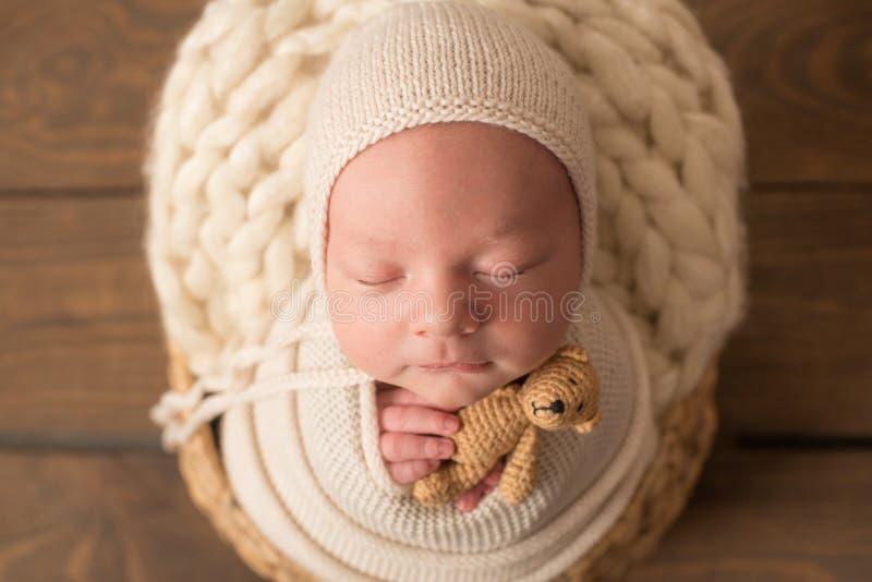 Bébé nouveau-né mignon en chapeau tricoté dans un panier en bois et avec un petit jouet à l'ours photographie stock libre de droits