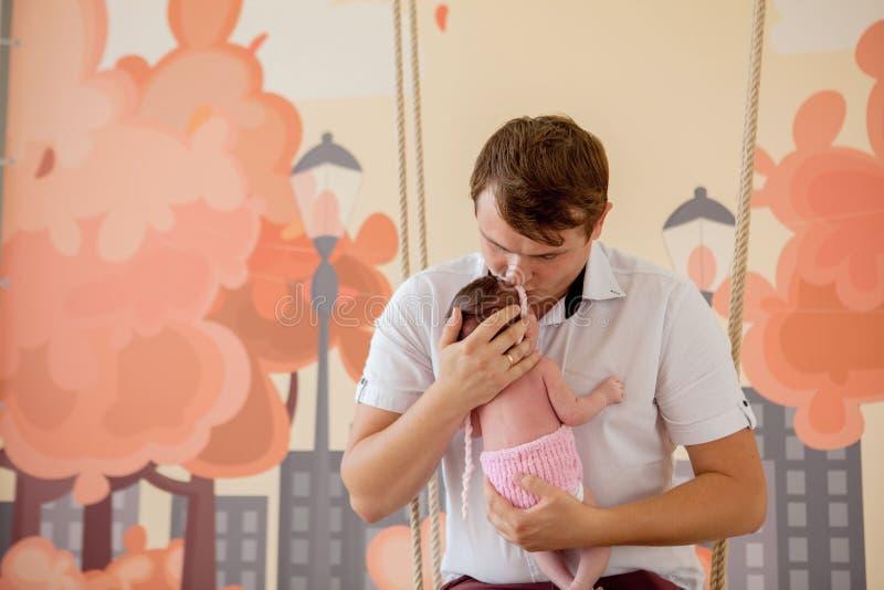 Bébé nouveau-né mignon se trouvant sur ses mains du ` s de père, à la maison photographie stock