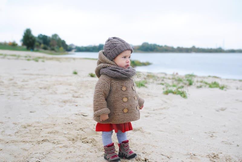Bébé observant à l'eau, au lac ou à la rivière, visage sérieux, saison froide, automne images libres de droits