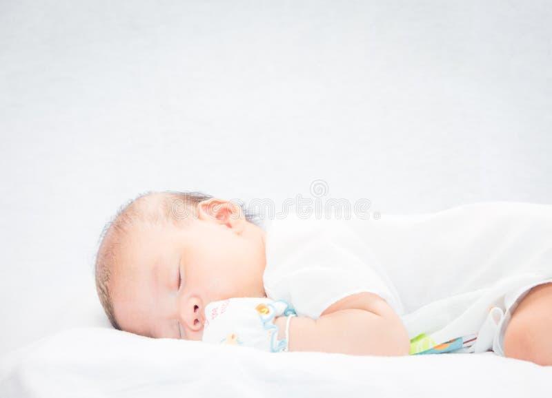 Bébé paisible se trouvant sur un lit tout en dormant photo stock