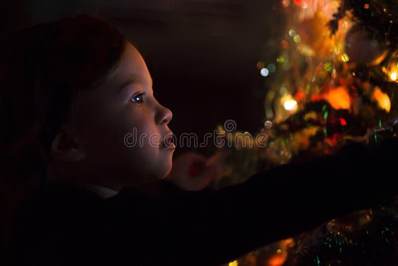 Bébé par l'arbre de Noël la nuit image stock