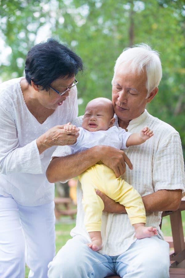 Bébé pleurant asiatique soulagé par des grands-parents photo libre de droits
