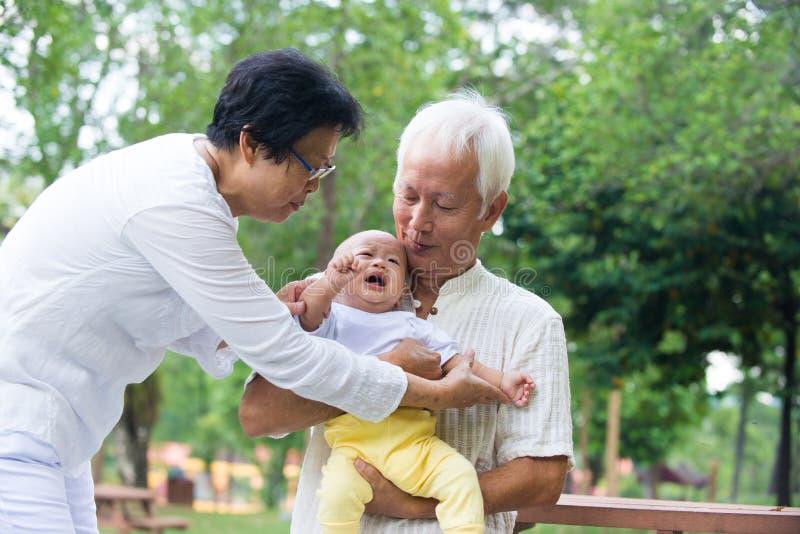 Bébé pleurant asiatique soulagé par des grands-parents images stock