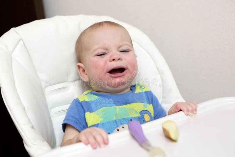 Bébé pleurant dans le highchair image stock