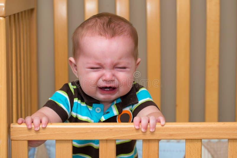 Bébé pleurant se tenant dans sa huche image stock
