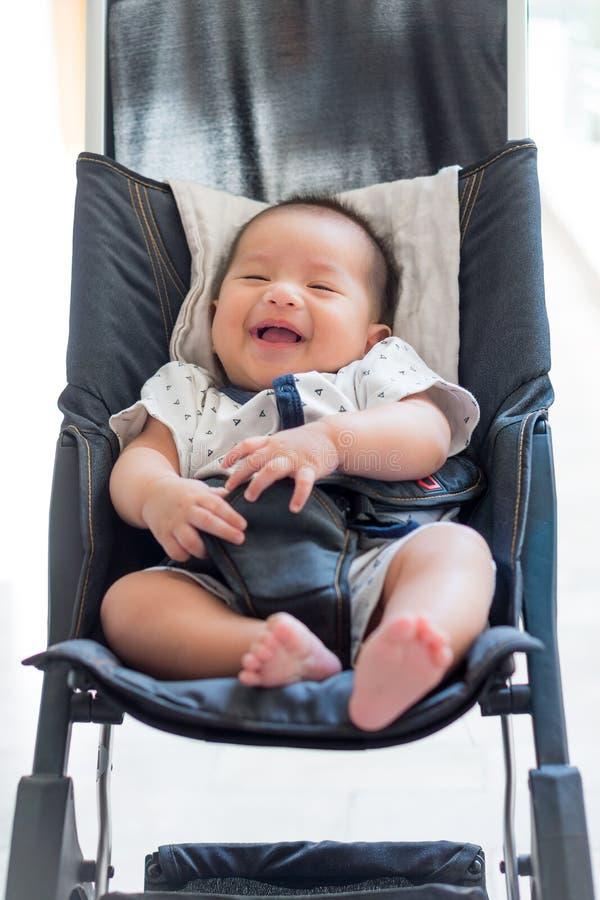 Bébé riant dans une voiture landau image stock