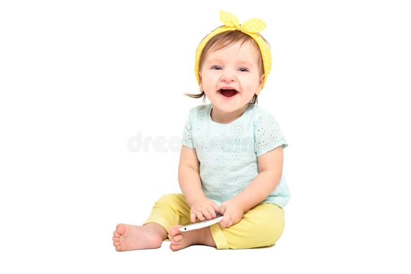 Bébé riant mignon, s'asseyant avec un téléphone portable image libre de droits