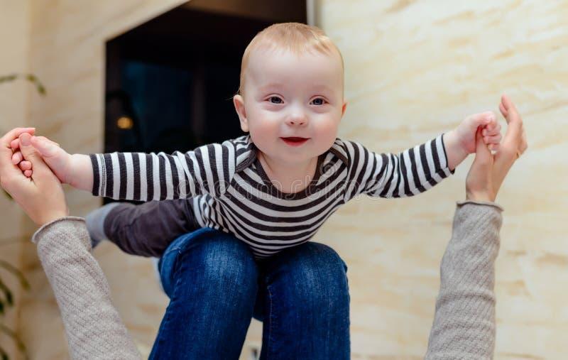 Bébé riant nerveusement sur des genoux d'adulte image libre de droits