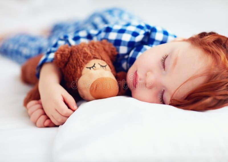 Bébé roux adorable d'enfant en bas âge dans des pyjamas de flanelle dormant avec le jouet de réchauffeur de peluche photo libre de droits