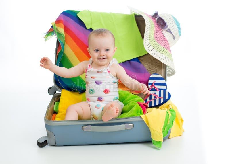 Bébé s'asseyant dans le tronc avec des choses pour le voyage de vacances image stock