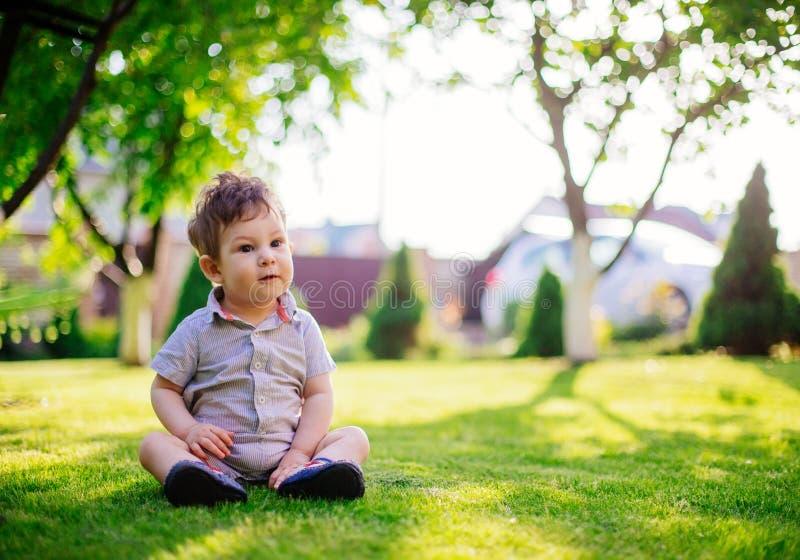 Bébé s'asseyant sur l'herbe photo stock