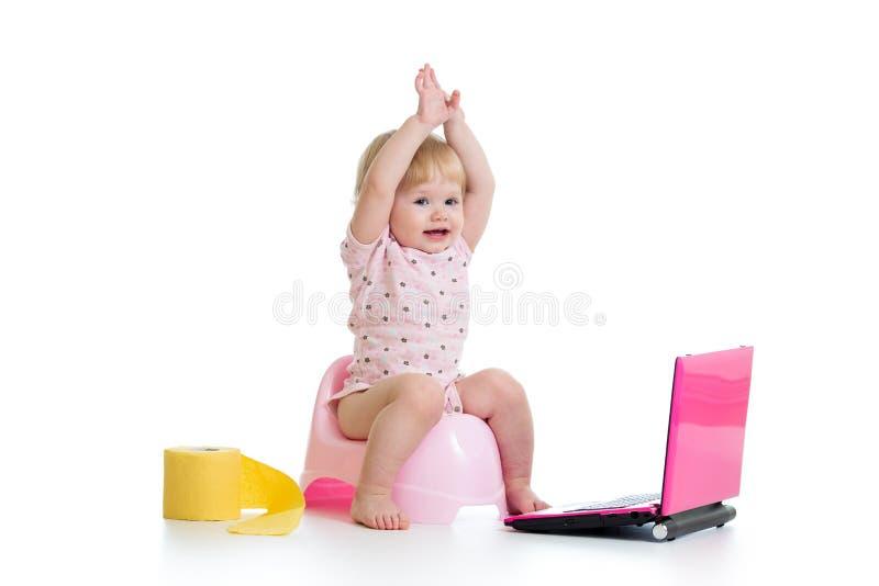 Bébé s'asseyant sur le chamberpot avec le carnet photos stock