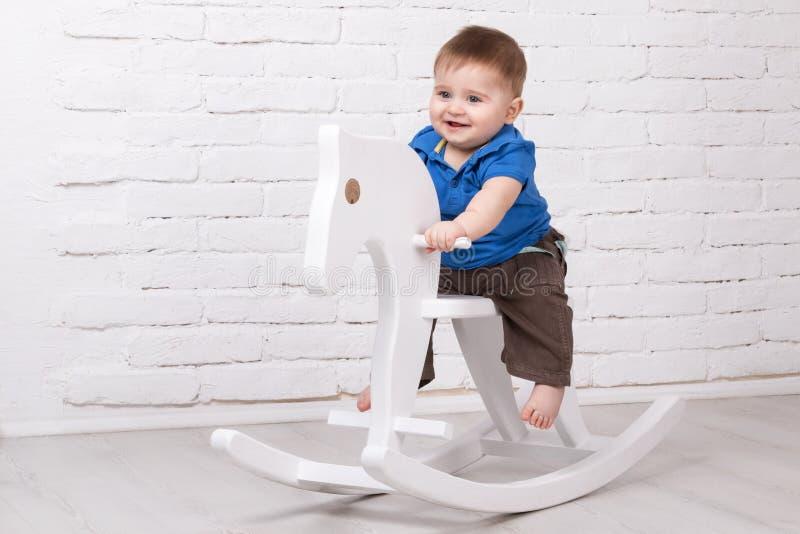 Bébé s'asseyant sur le cheval de jouet images stock