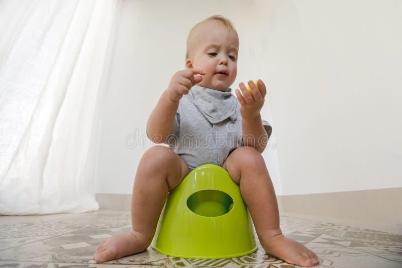 Bébé s'asseyant sur le pot et mangeant des légumes photographie stock