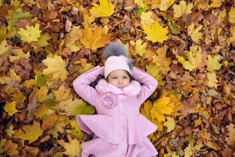 Bébé se trouvant sur des feuilles d'automne dans le manteau rose photos stock