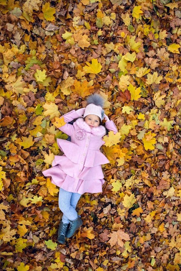 Bébé se trouvant sur des feuilles d'automne dans le manteau rose image stock