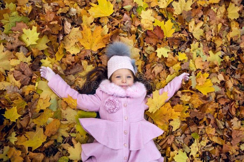Bébé se trouvant sur des feuilles d'automne dans le manteau rose images stock