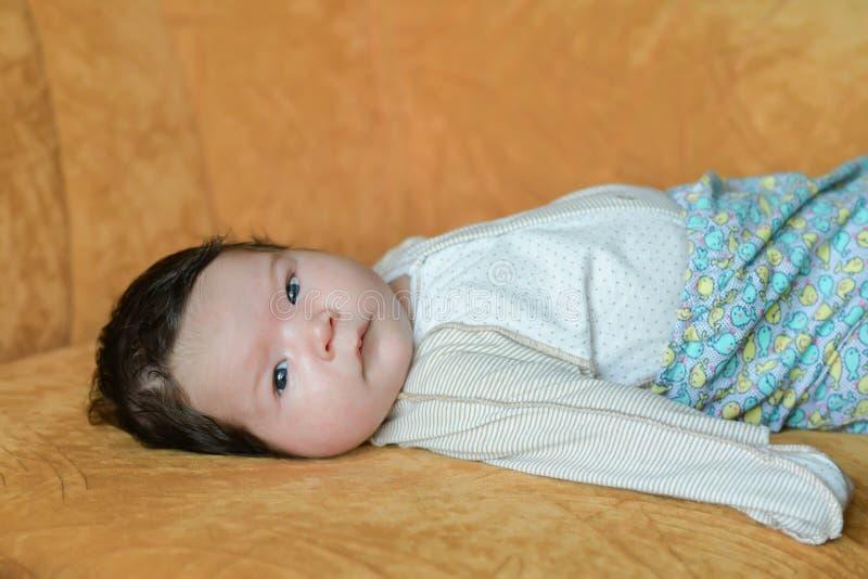 Bébé se trouvant sur le divan concept de famille, de condition parentale et de maternité - fin de la mère jouant avec peu de fill photographie stock libre de droits