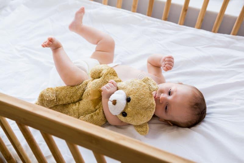 Bébé se trouvant sur le lit de bébé photographie stock libre de droits
