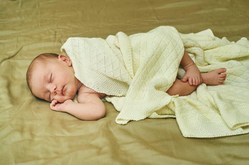 Bébé se trouvant sur le sofa et couvert de châle images stock