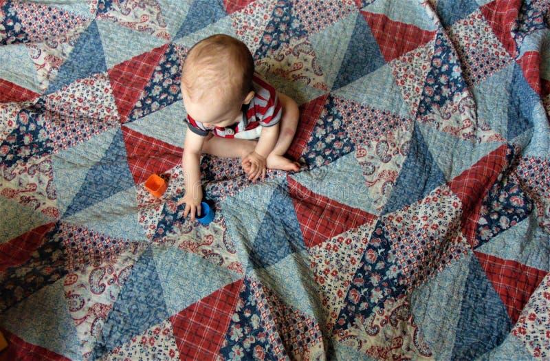 Bébé sur l'édredon de patchwork multicolore photo stock