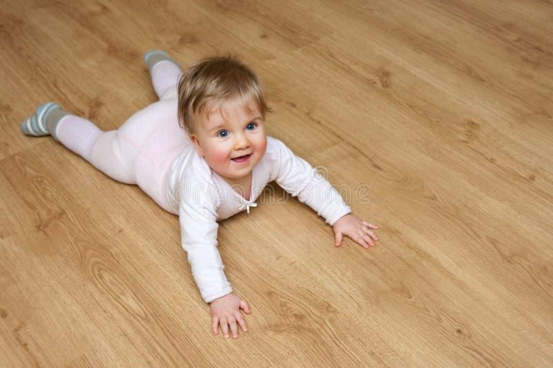 Bébé sur l'étage en bois photo stock