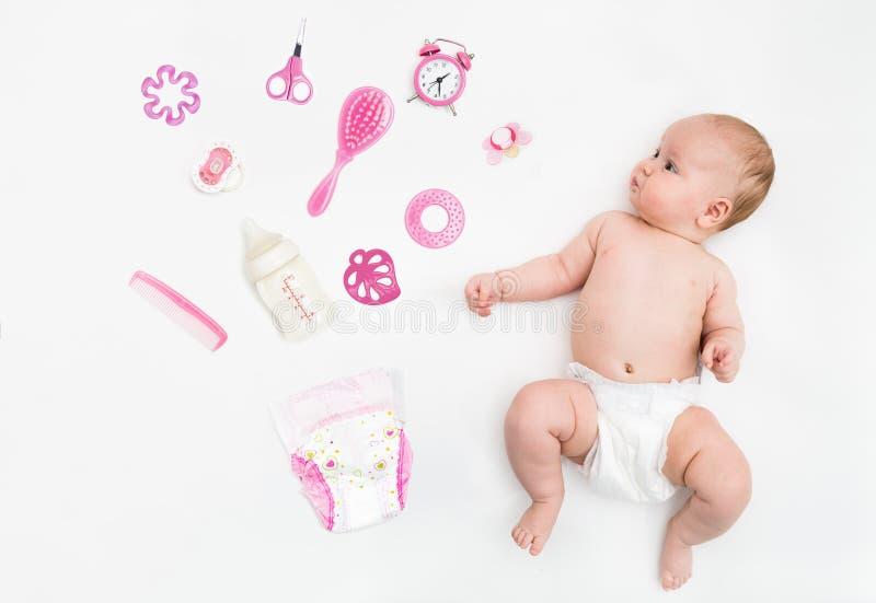 Bébé sur le fond blanc avec l'habillement, les articles de toilette, les jouets et les accessoires de soins de santé pour des fil photo stock