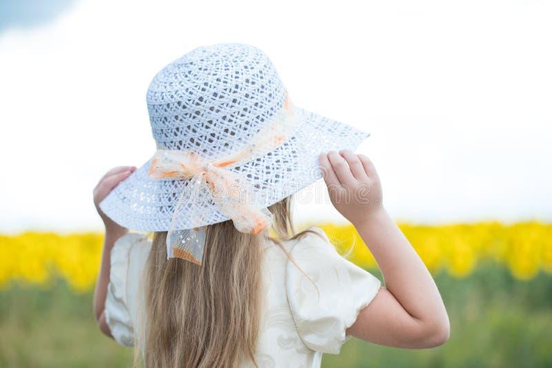 Bébé sur une promenade dans un domaine avec des dans-fleurs photographie stock libre de droits