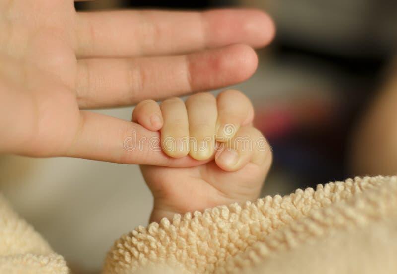 Bébé tenant le doigt de la mère photo stock