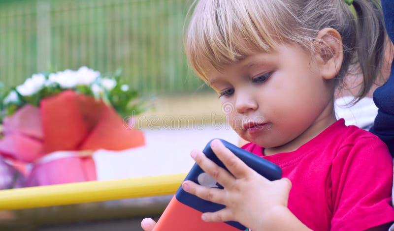 Bébé tenant un téléphone portable Petite fille caucasienne jouant avec le smartphone en parc d'été Enfant apprenant comment à photo stock
