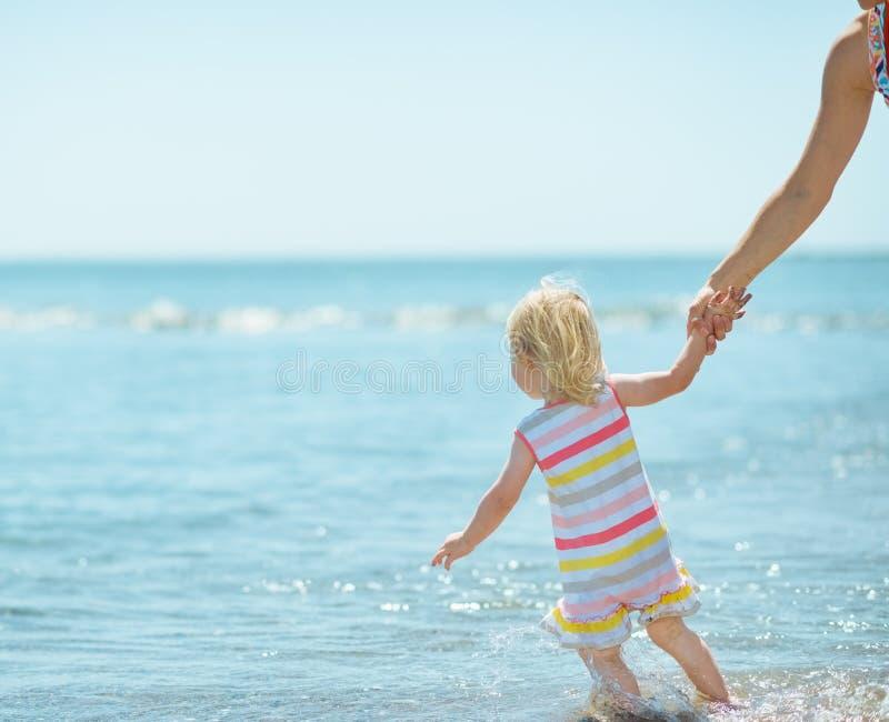 Bébé tirant la mère en mer photos libres de droits