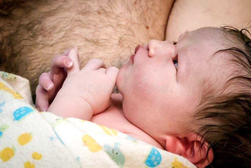 Bébé tout neuf tenu par le papa image stock
