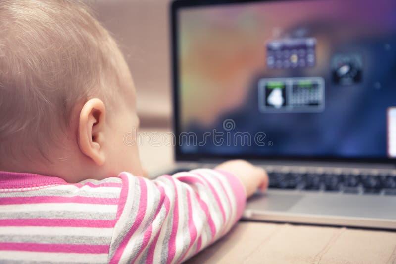 Bébé travaillant sur l'ordinateur portable avec la main atteignant au touchpad image stock