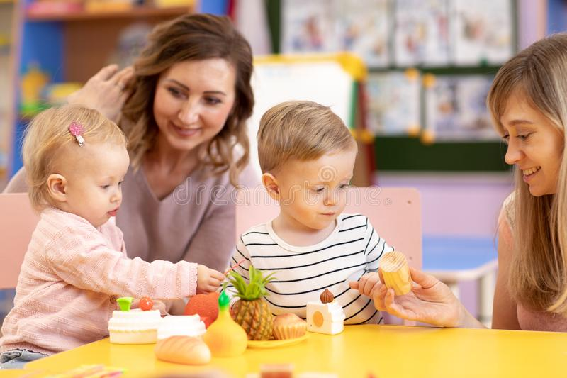 Bébés jouant avec des jouets à l'école de montessori de pièce de crèche images stock