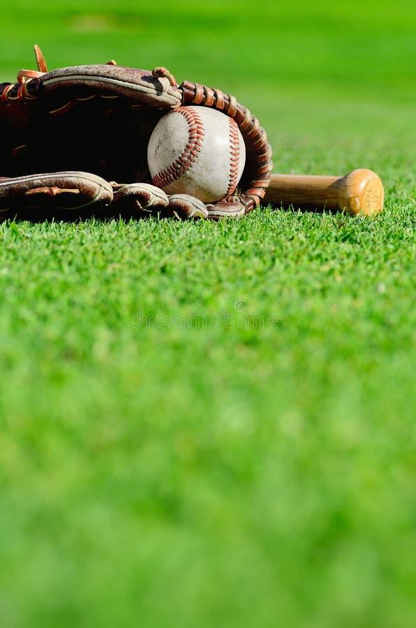 Béisbol en mitón con el palo foto de archivo