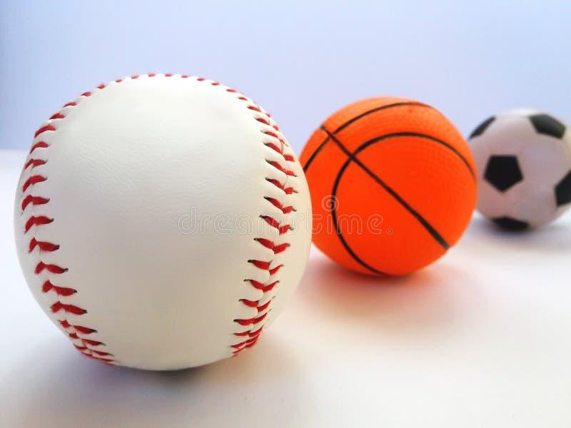 Béisbol, fútbol, baloncesto Tres bolas de los deportes en un fondo ligero para las tarjetas, banderas, aviadores imagen de archivo