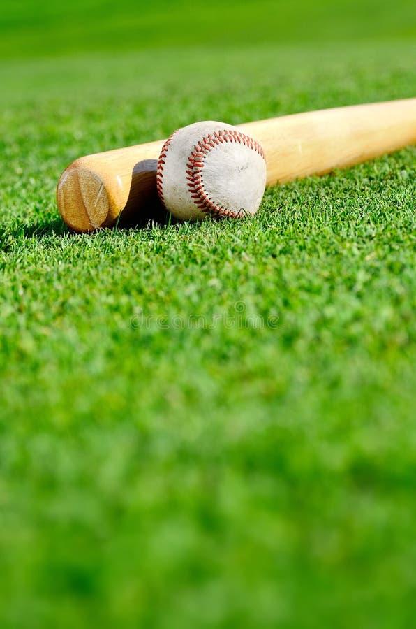 Béisbol y palo en campo fotos de archivo