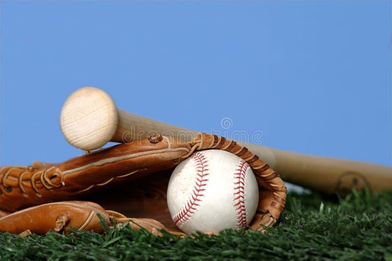 Béisbol y palo en hierba imagenes de archivo