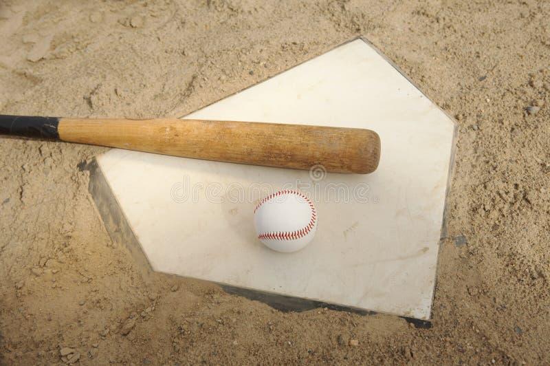Béisbol y palo en la placa casera fotografía de archivo