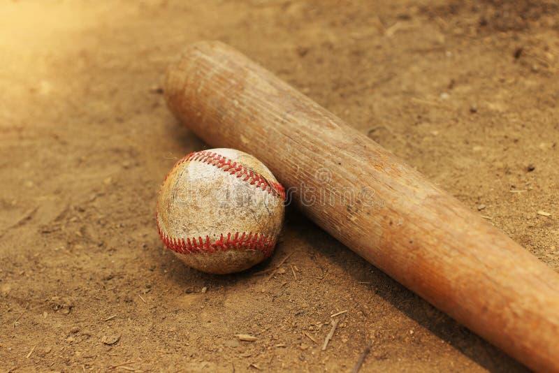 Béisbol y palo que ponen en la suciedad fotografía de archivo