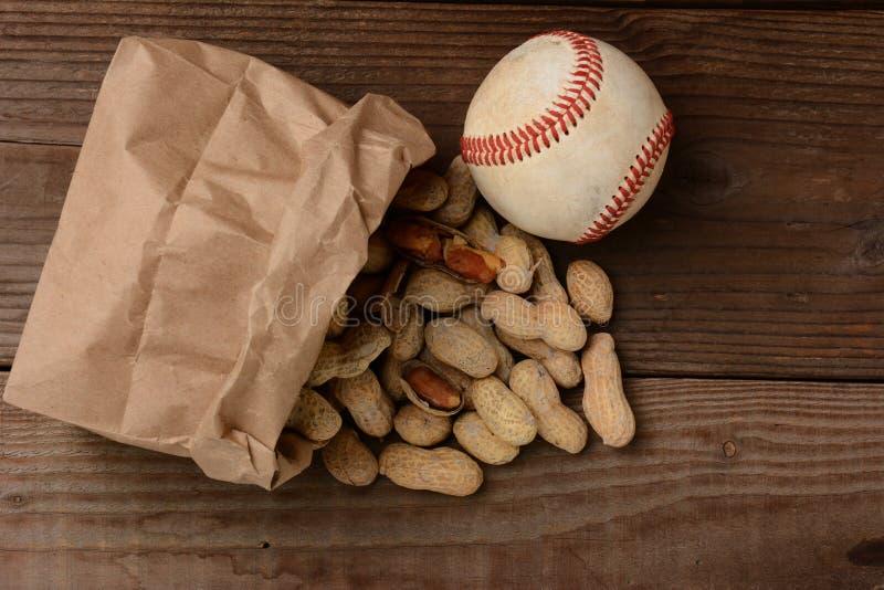 Béisbol y un bolso con los cacahuetes que se derraman hacia fuera fotografía de archivo